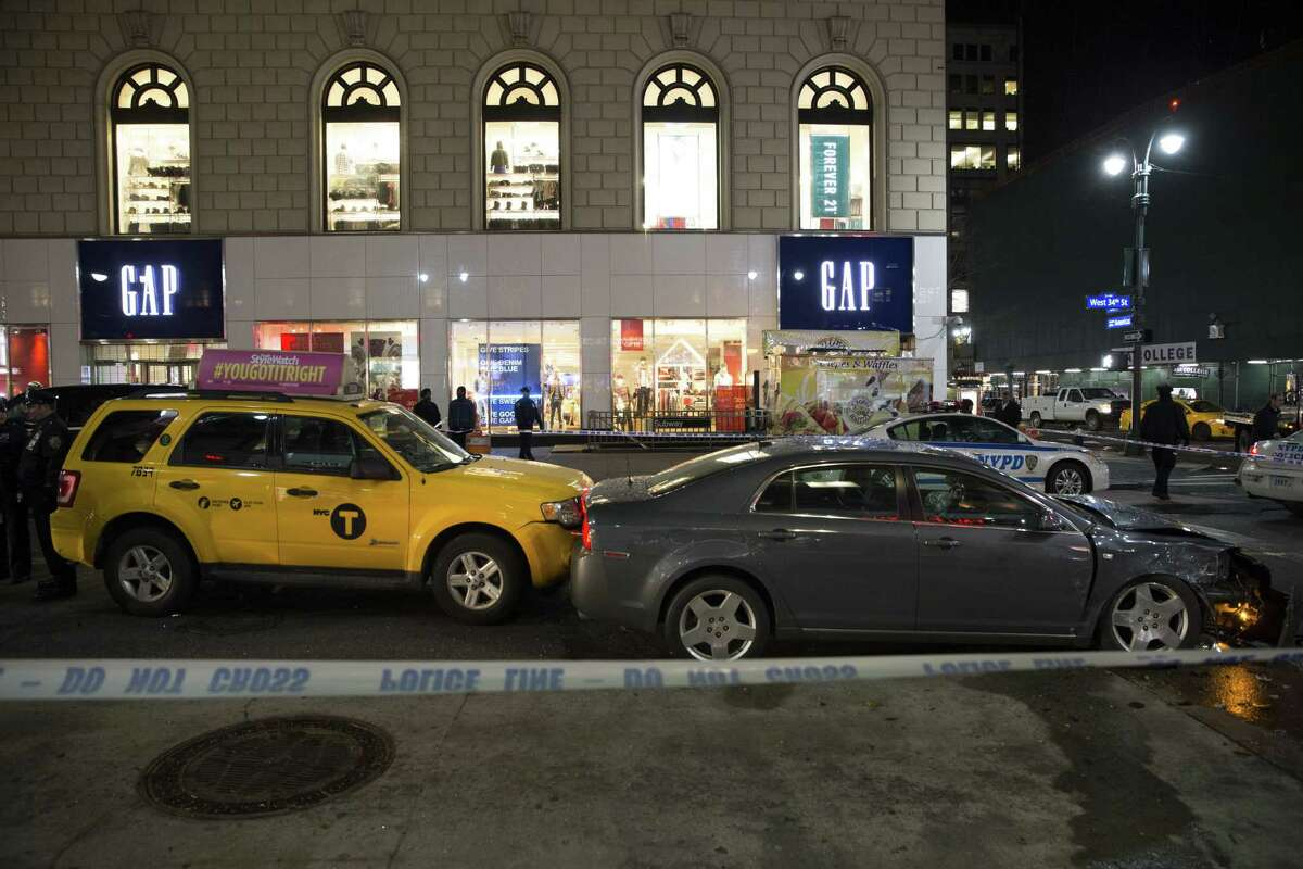 Vehicles involved in an accident are surrounded by police tape on 34th Street, Thursday, Dec. 11, 2014, in New York. Six people were hurt when the car jumped a curb in midtown Manhattan and struck a group of people around 10 p.m. A fire department spokesman says the injured were taken to Bellevue hospital with serious but non-life threatening injuries. (AP Photo/John Minchillo)