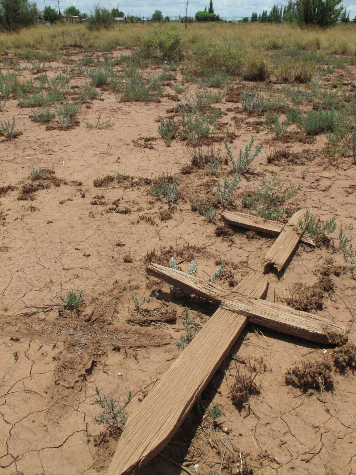 This July 9, 2014 photos shows wooden crosses lying in a dusty cemetery in Winslow, Arizona. Local historic preservation Commissioner Gail Sadler has made it her mission to unearth the identities of roughly 600 people buried there and help their descendants reconnect with a lost part of their history. (AP Photo/Felicia Fonseca)