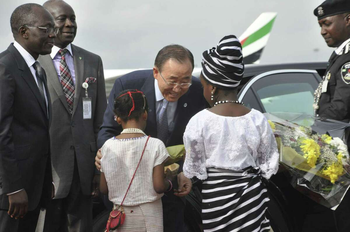 U.N Secretary General Ban Ki-Moon, center. receives flowers from a girl upon his arrival at Nnamdi Azikiwe International airport in Abuja, Nigeria Sunday, Aug. 23, 2015. U.N. Secretary General Ban Ki-moon arrived in Nigeria Sunday to mark the Boko Haram bombing of his organization's headquarters and focus new attention on 219 schoolgirls held by the extremist group. (AP Photo/Gbemiga Olamikan)