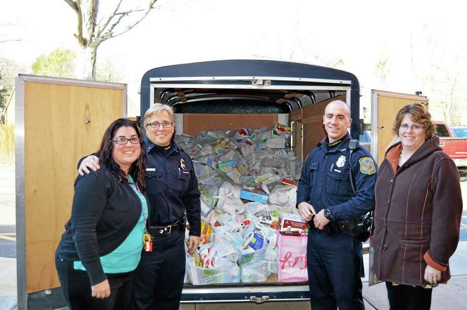 From left are Joy Hollister, Town of Cromwell Human Services Director; Police Chief Denise Lamontagne, Officer Jeremy Perlini, Lisa Olson, Town of Cromwell Human Services assistant and food bank coordinator. Photo: Photos Courtesy Cromwell Police