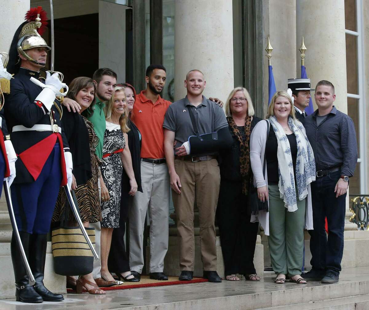 Anthony Sadler, center with orange shirt, a senior at Sacramento State University in California, U.S. Airman Spencer Stone, fourth from right, U.S. National Guardsman from Roseburg, Ore., Alek Skarlatos, third from left, and their families pose with U.S. Ambassador to France Jane D. Hartley, fourth from left, on the steps of the Elysee Palace before being awarded with the Legion of Honor Monday in Paris, France.