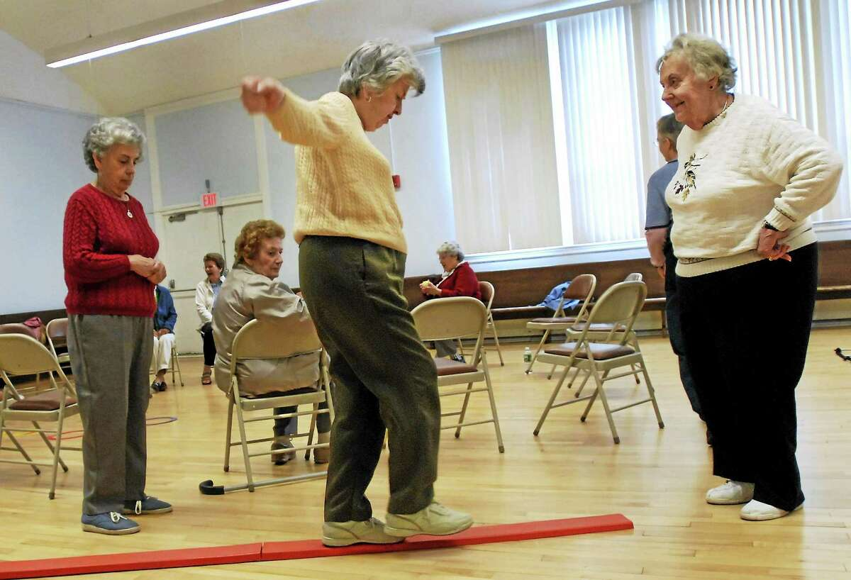 Shirley Ristau, right, coaches Johanna O'Neill, center, through a balance obstacle course while O'Neill's sister, Mary O'Neill, left, looks on during a fall prevention demonstration class at the Manchester Senior Center in Manchester, Conn.