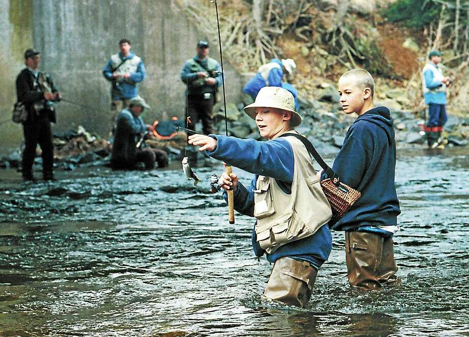 In this file photo, Mark Bennardo of Berlin hauls in a young salmon while fishing with his friend Andrew Dwyer, also of Berlin, on opening day at Salmon River in East Hampton. Photo: Press File Photo
