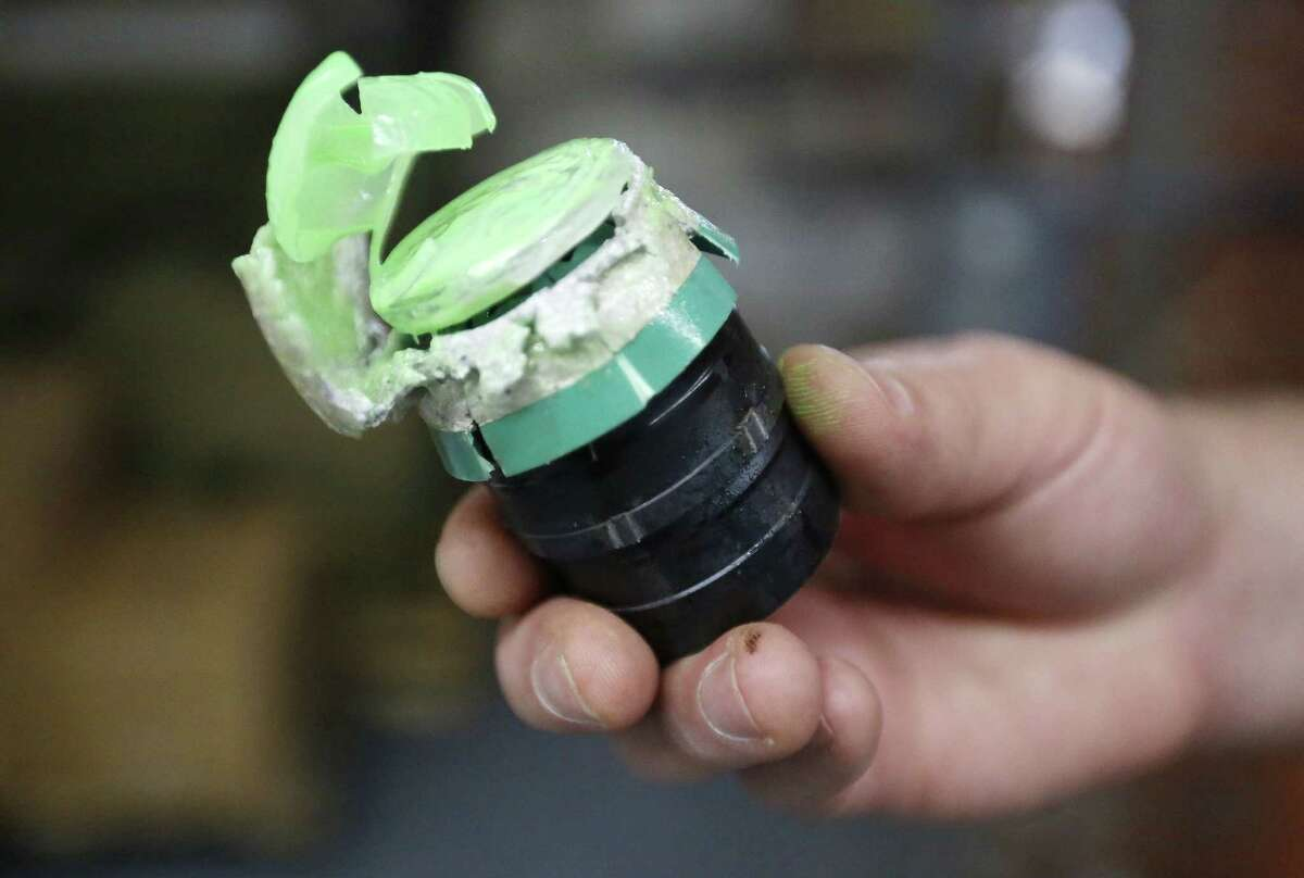 In this July 30, 2015 photo, a 40mm Blunt Impact Projectile that releases green marking powder on impact is displayed after being fired at a test dummy at Micron Products, Inc., in Fitchburg, Mass.