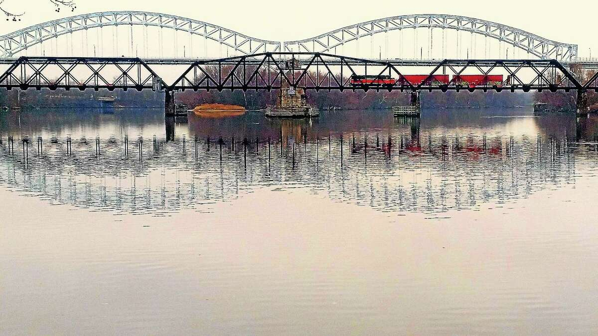 A train passes over a calm Connecticut River Monday on the Arrigoni Bridge as seen from Middletown. A late-arriving winter comes on the heels of the warmest autumn on record, according to the National Weather Service.