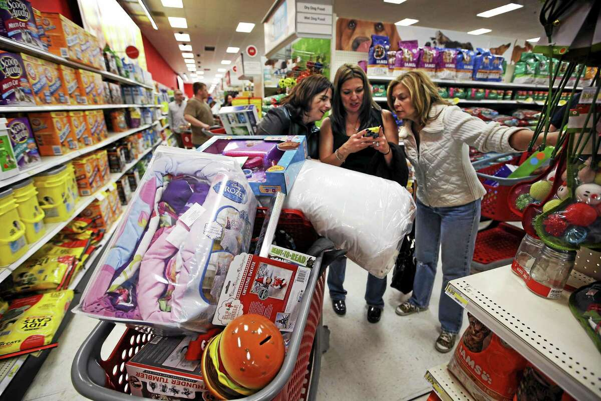In this Nov. 28, 2014 photo, Target shoppers Kelly Foley, left, Debbie Winslow, center, and Ann Rich use a smartphone to look at a competitor's prices.