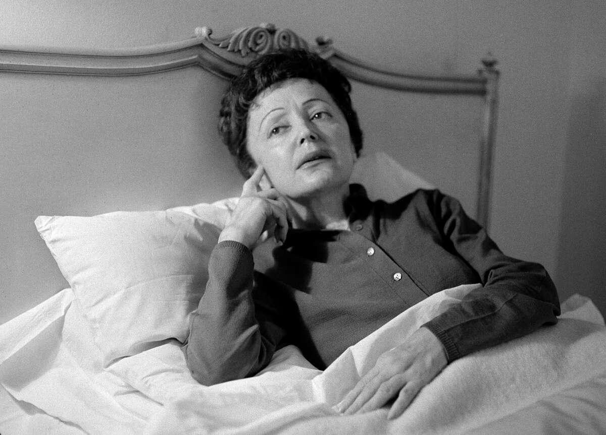 """FILE - In this Feb. 20, 1959 file photo, French songstress Edith Piaf props up in bed after an undisclosed illness resulted in the cancellation of scheduled performances at the Waldorf-Astoria Hotel in New York. Piaf, famous for her hit """"La Vie En Rose,"""" would have turned 100 on Dec. 19, 2015. At only 4 feet 8 inches, her voice was strong and distinctive, a trembling alto wail that became the voice of the Paris working class. Piaf died on Oct. 10, 1963, from exhaustion and liver disease at the age of 47."""