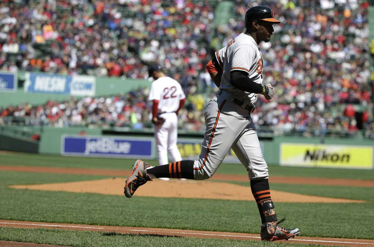 The Orioles' Adam Jones, right, rounds the bases after hitting a two-run home run off Rick Porcello in the first inning on Sunday.