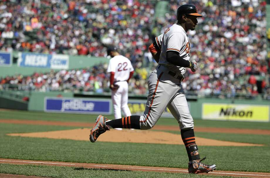 The Orioles' Adam Jones, right, rounds the bases after hitting a two-run home run off Rick Porcello in the first inning on Sunday. Photo: Steven Senne — The Associated Press  / AP