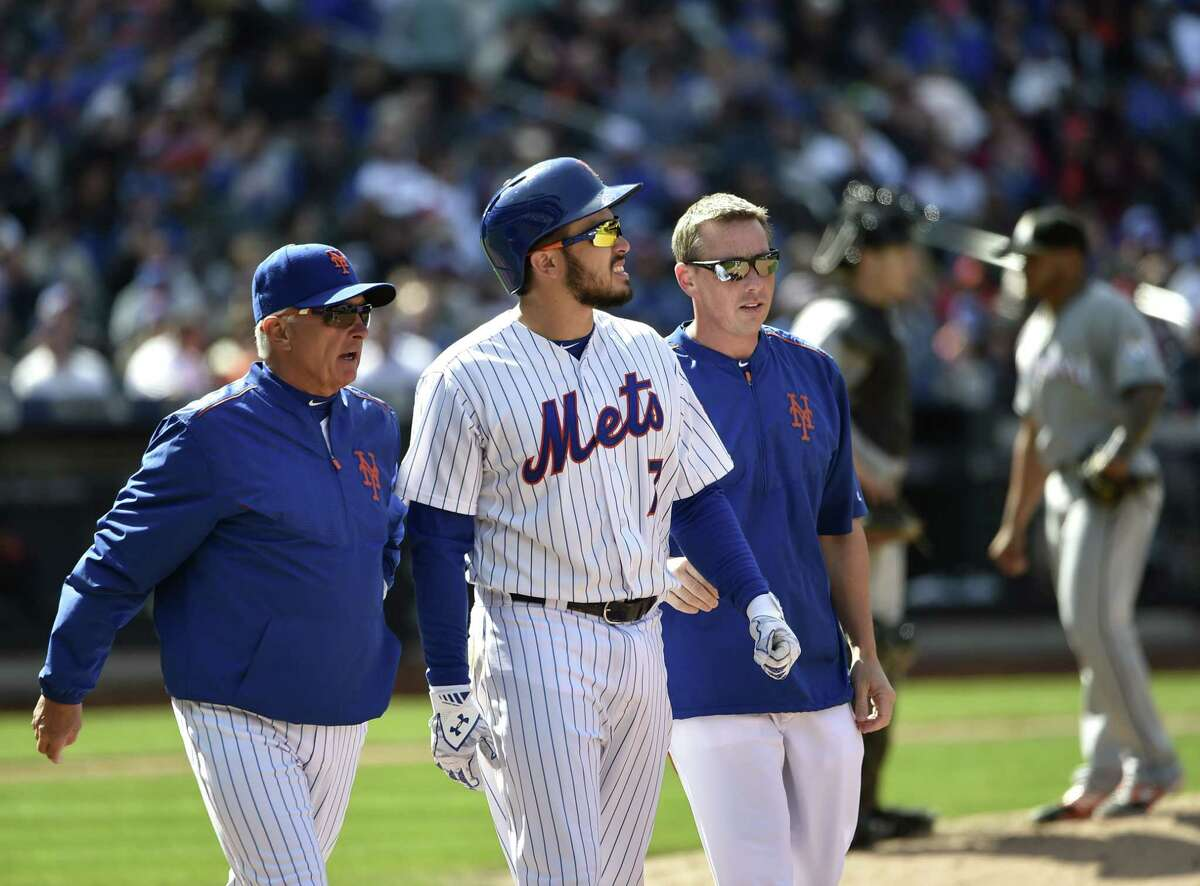 Mets manager Terry Collins, left, and a Mets trainer talk with catcher Travis d'Arnaud after he was hit by a pitch thrown in the seventh inning on Sunday. d'Arnaud left the game with a fractured right hand.