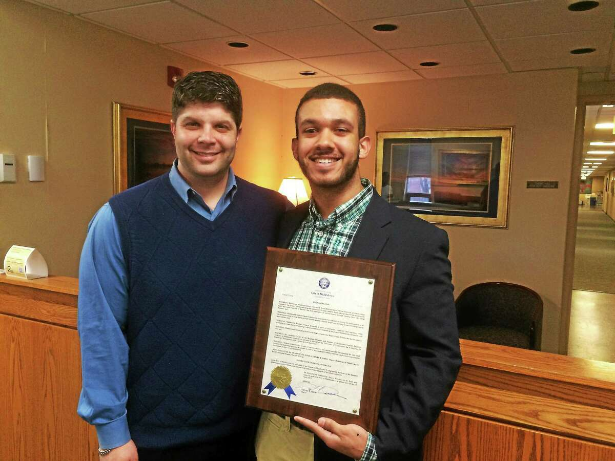 University of Connecticut business student Anthony LeClair of Middletown poses with Mayor Dan Drew after receiving a certificate from the city commending him for his entrepreneurial goals.