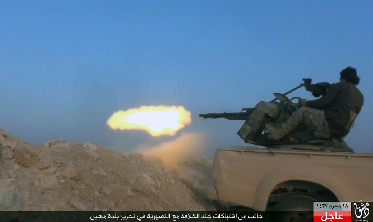 """This file image posted Nov. 1, 2015, by supporters of the Islamic State militant group on an anonymous photo sharing website, shows an Islamic State fighter firing his weapon during a battle against Syrian government troops in the village of Mahin, central Homs province, Syria. Decades of reckless arms trading and poorly regulated arms flow into Iraq have contributed to the Islamic State group's """"large and lethal arsenal"""" being used to commit war crimes on a massive scale in Iraq and Syria, an international rights group said Tuesday, Dec. 8. The Arabic banner reads, """"A side of the clashes between the soldiers of the caliphate and Alawites to liberate the village of Mahin."""""""