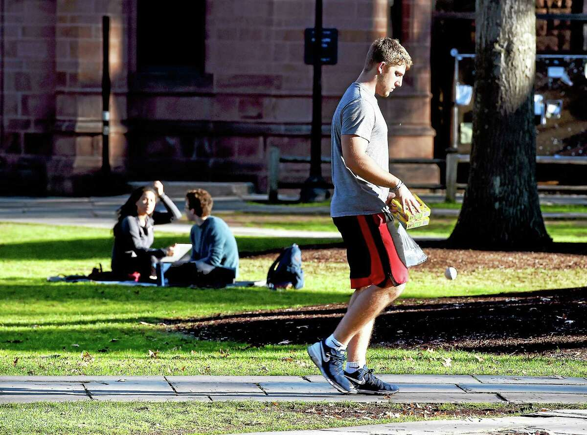 Yale freshman Quintin Herbert walks through Yale University's Old Campus in New Haven during finals week Tuesday. Herbert is from Cincinnati, Ohio, where the weather has been just as warm.
