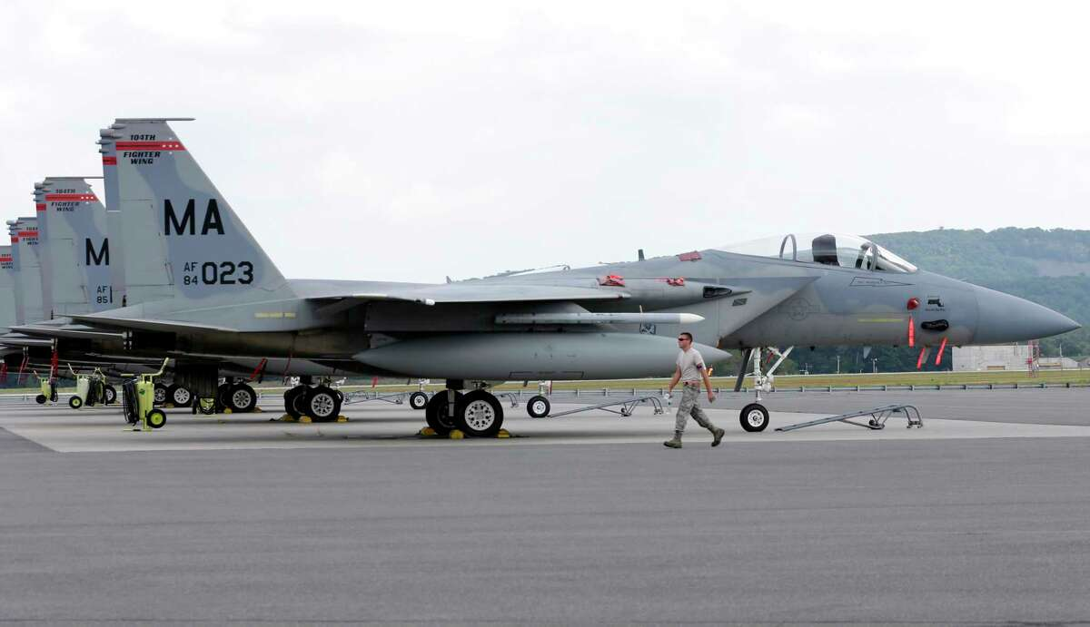 A Massachusetts Air National Guard aircraft maintainer walks past a row of F-15C fighter aircraft at Barnes Air National Guard Base, in Westfield, Mass., Wednesday, Aug. 27, 2014.