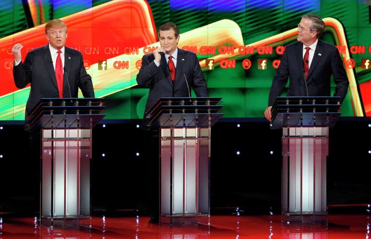 Donald Trump, left, speaks as Ted Cruz, center, and Jeb Bush watch during the CNN Republican presidential debate at the Venetian Hotel & Casino Tuesday in Las Vegas.