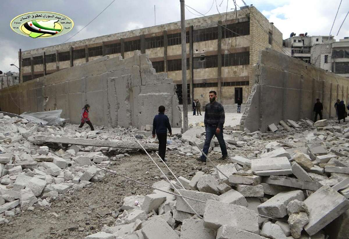 This photo posted by the anti-government activist website of the Syrian Observatory for Human Rights, which has been verified and is consistent with other AP reporting, shows Syrians walking in wreckage in front of a school that was attacked by an airstrike, in Ansari neighborhood in Aleppo, Syria, April 12.