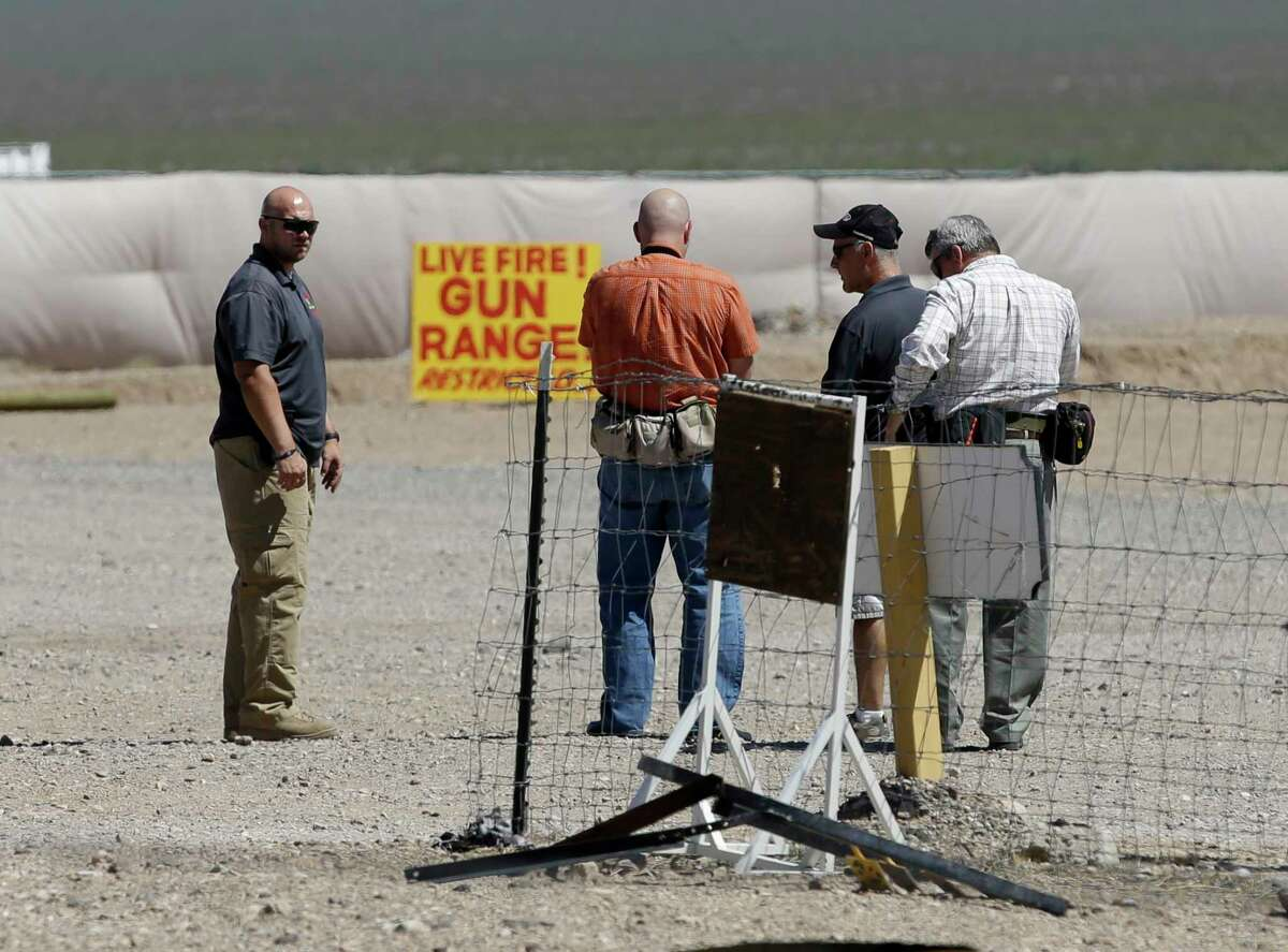 People are seen at the Last Stop outdoor shooting range Wednesday, Aug. 27, 2014, in White Hills, Ariz. Gun range instructor Charles Vacca was accidentally killed Monday, Aug. 25, 2014 at the range by a 9-year-old with an Uzi submachine gun. (AP Photo/John Locher)