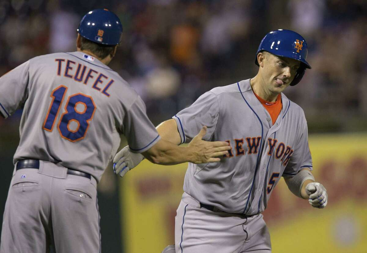 New York Mets' David Wright, right, passes third base coach Tim Teufel, left, while scoring on a home run by Wilmer Flores in the fourth inning of a baseball game with the Philadelphia Phillies, Monday, Aug. 24, 2015, in Philadelphia. (AP Photo/Laurence Kesterson)