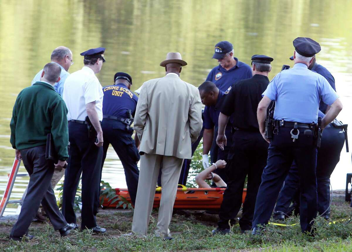 Philadelphia police and other law enforcement officials view a body pulled from the Schuylkill River in Fairmount Park in Philadelphia, Wednesday, Aug. 27, 2014. The bound bodies of two people were found in the river Wednesday, and a third man who said he managed to free himself is being treated at a hospital for stab wounds, police said.