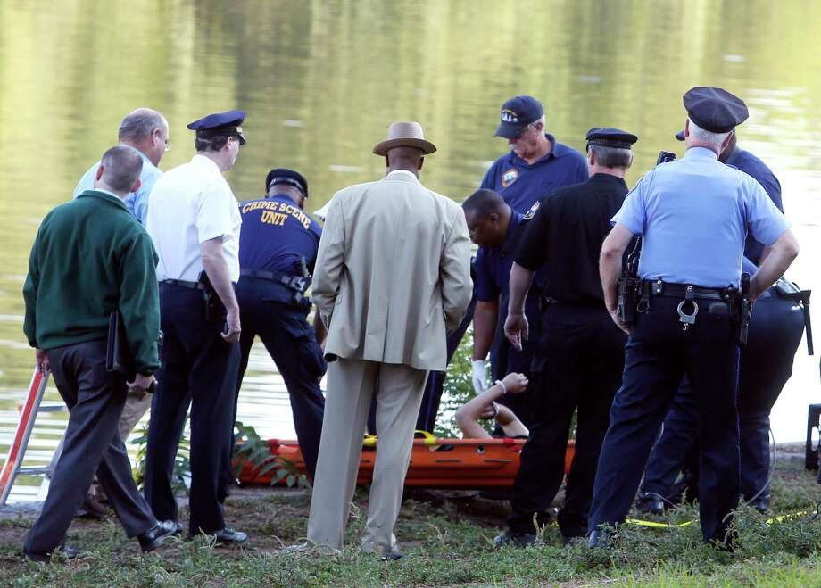 Philadelphia police and other law enforcement officials view a body pulled from the Schuylkill River in Fairmount Park in Philadelphia, Wednesday, Aug. 27, 2014.  The bound bodies of two people were found in the river Wednesday, and a third man who said he managed to free himself is being treated at a hospital for stab wounds, police said. Photo: AP Photo/Jacqueline Larma / AP