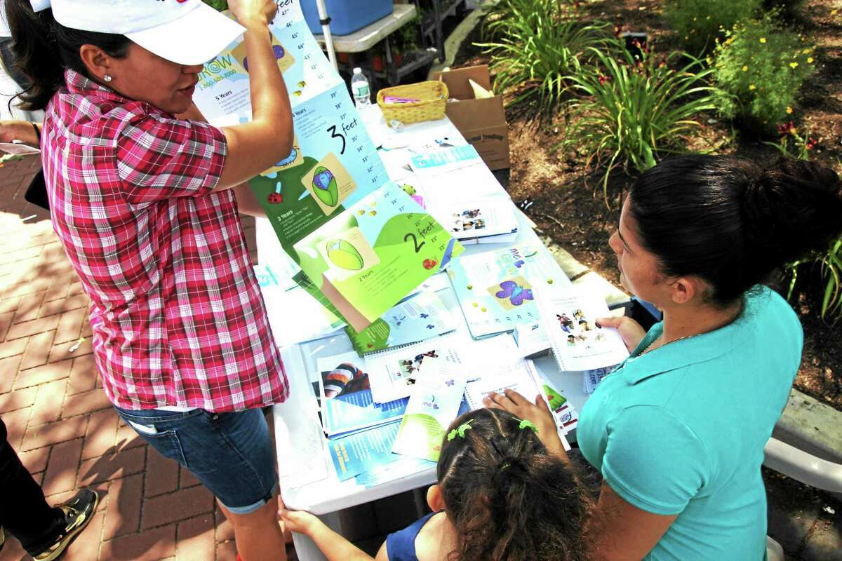 Elizabeth Quinonez shows early-childhood developmental charts with parents at the Danbury Farmers Market in July. Quinonez, community coordinator for Danbury's Promise for Children partnership, has recruited about 20 parents who speak English and Spanish to spread the word about free programs for young children.