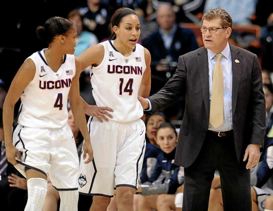 Connecticut head coach Geno Auriemma, right, speaks with Moriah Jefferson, left, and Bria Hartley, center, during the first half of an NCAA college basketball game against Rutgers in the semifinals of the American Athletic Conference women's tournament, Sunday, March 9, 2014, in Uncasville, Conn. (AP Photo/Jessica Hill) Photo: AP / FR125654 AP