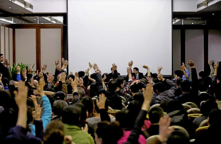 Relatives of Chinese passengers aboard the missing Malaysia Airlines Flight MH370 raise their hands to question Malaysian government officials during a news briefing held by the airlines at a hotel ballroom in Beijing Monday, March 17, 2014. The search for the missing Malaysian jet pushed deep into the northern and southern hemispheres Monday as Australia took the lead in scouring the seas of the southern Indian Ocean and Kazakhstan - about 10,000 miles to the northwest - answered Malaysia's call for help in the unprecedented hunt. (AP Photo/Andy Wong) Photo: AP / AP