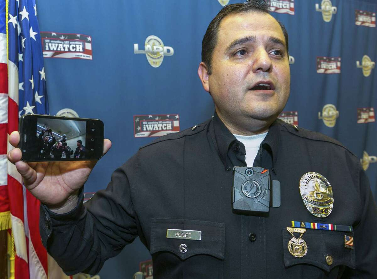 Los Angeles Police Sgt. Dan Gomez demonstrates a video feed from his on-body camera into his cellphone during a news conference in Los Angeles on Tuesday, Dec. 16, 2014. Mayor Eric Garcetti announced a plan Tuesday to equip 7,000 Los Angeles police officers with on-body cameras by summer 2015, making LA's police department the nation's largest law enforcement agency to move forward with such an ambitious expansion of the technology. (AP Photo/Damian Dovarganes)