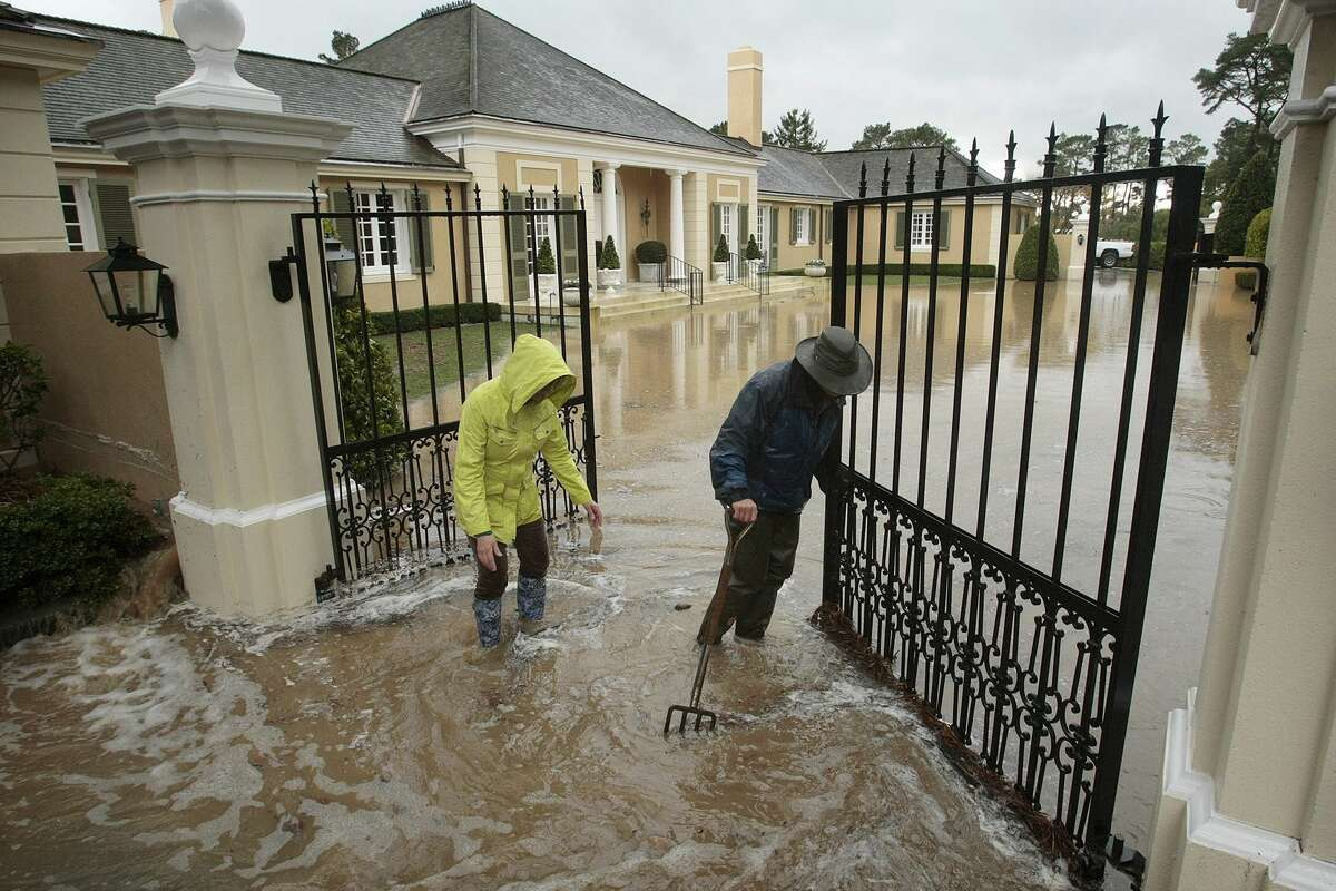 Property managers Valorie, left, and Alan Lambert, right, work to clear drains to minimize flooding at a client's home Monday, Dec. 15, 2014, in Pebble Beach, Calif. A new storm dumped more rain on already waterlogged parts of Northern California, causing minor road flooding, scattered power outages and airport delays. The rain was coming down hard in the San Francisco Bay Area, making for a treacherous commute. A landslide closed both directions of a highway in Fremont.(AP Photo/Monterey Herald, Vern Fisher)