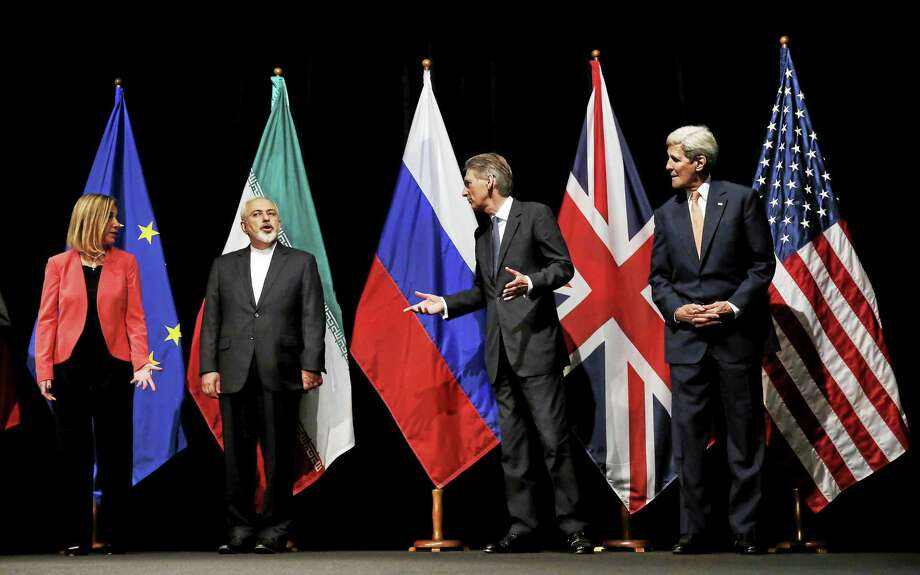 In this July 14 file photo, British Foreign Secretary Philip Hammond, second right, U.S. Secretary of State John Kerry, right, and European Union High Representative for Foreign Affairs and Security Policy Federica Mogherini, left, talk to Iranian Foreign Minister Mohammad Javad Zarif as the wait for Russian Foreign Minister Sergey Lavrov, not pictured, for a group picture at the Vienna International Center in Vienna, Austria. After 18 days of intense and often fractious negotiation, world powers and Iran struck a landmark deal Tuesday to curb Iran's nuclear program in exchange for billions of dollars in relief from international sanctions — an agreement designed to avert the threat of a nuclear-armed Iran and another U.S. military intervention in the Muslim world. Photo: Associated Press  / Pool Reuters