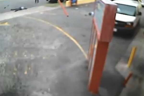 """In this still image from a security video made on Jan. 29, 2015, and provided by the Los Angeles Superior Court where it was entered into evidence, two men lie on the ground after an SUV driven by rap music mogul Marion """"Suge"""" Knight ran over them at a fast food restaurant in Compton, Calif., near Los Angeles. Cle """"Bone"""" Sloan, top left, survived, but Terry Carter, partially obscured behind the sign, later died. A judge ruled on Thursday, April 16, 2015, that Knight will stand trial on murder and attempted-murder charges. (Los Angeles Superior Court via AP)"""
