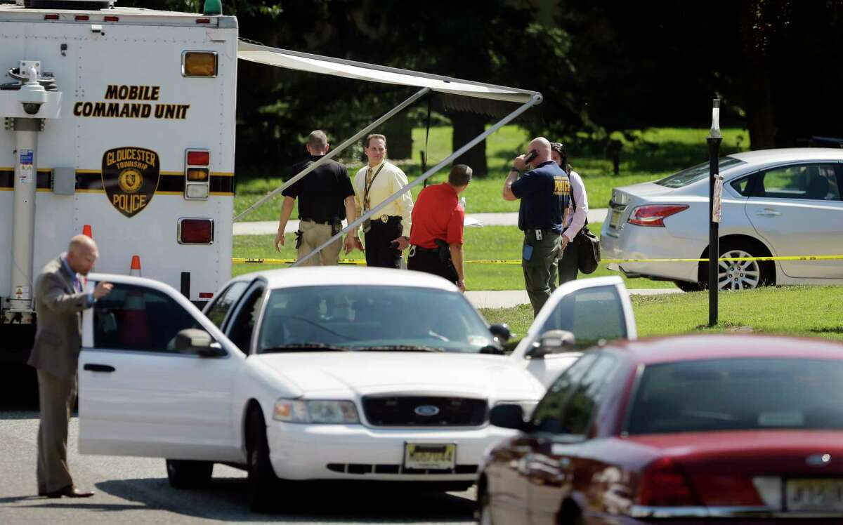 Investigators gather in front of a home where a shooting victim was found Wednesday, Aug. 27, 2014, in Glendora, N.J. (AP Photo/Mel Evans)
