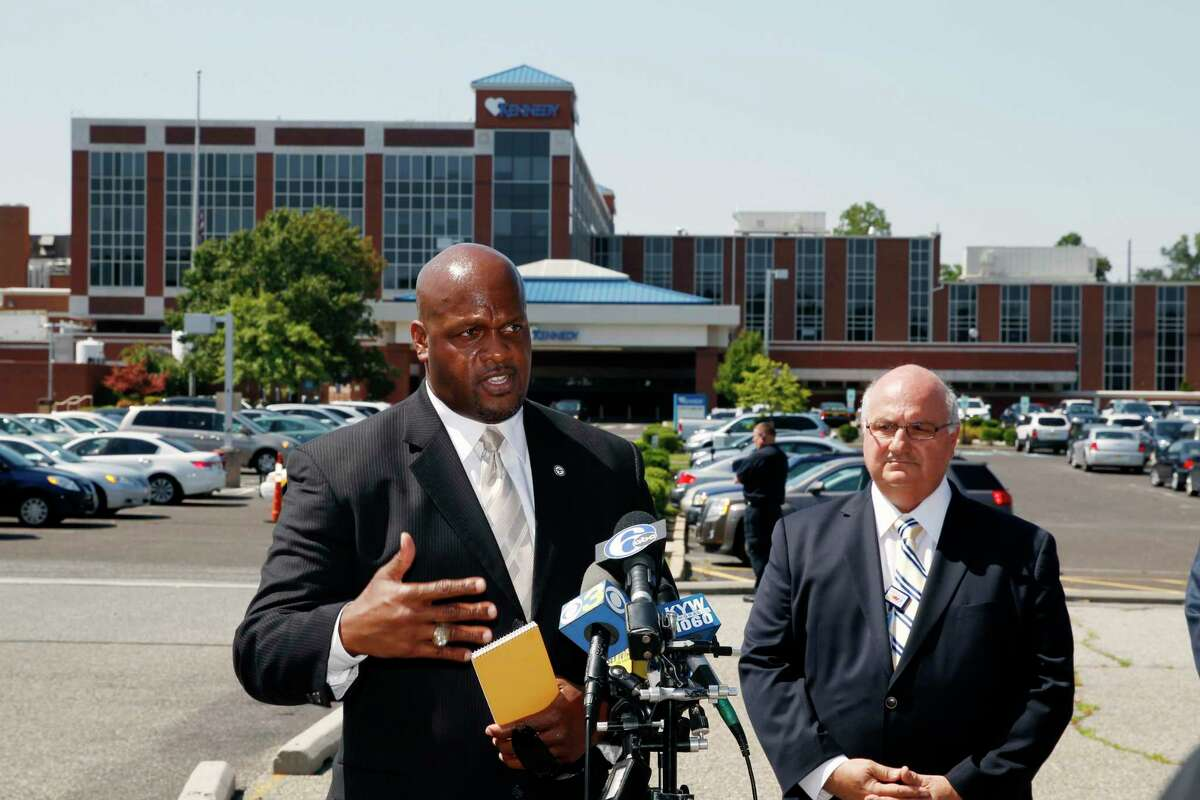 Camden County Prosecutor's Office Capt. Ron Moten, left, stands with in front of Kennedy Hospital with hospital chief of safety, David Condoluci, as he answers a question about shootings at the facility Wednesday, Aug. 27, 2014, in Stratford, N.J. (AP Photo/Mel Evans)