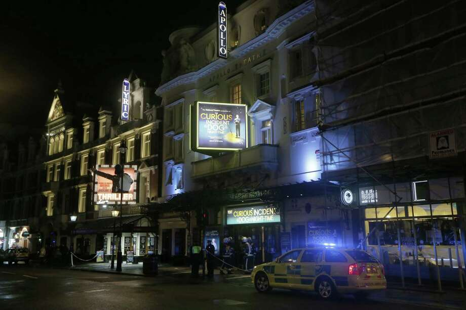 """FILE - A Thursday, Dec. 19, 2013 file photo showing firefighters exiting the Apollo Theatre, London, after its ceiling partially collapsed during a performance. London authorities say no one should be prosecuted over a mid-performance ceiling collapse at the Apollo Theatre last year that injured more than 80 people. Westminster Council said Wednesday, Dec. 17, 2014, that the accident was a result of the building's age and there had been no breach of the law. Seven people were seriously hurt and scores more slightly injured when chunks of plaster and wood fell from the theater ceiling during a performance of """"The Curious Incident of the Dog in the Night-time."""" (AP Photo/Sang Tan, File) Photo: AP / AP"""