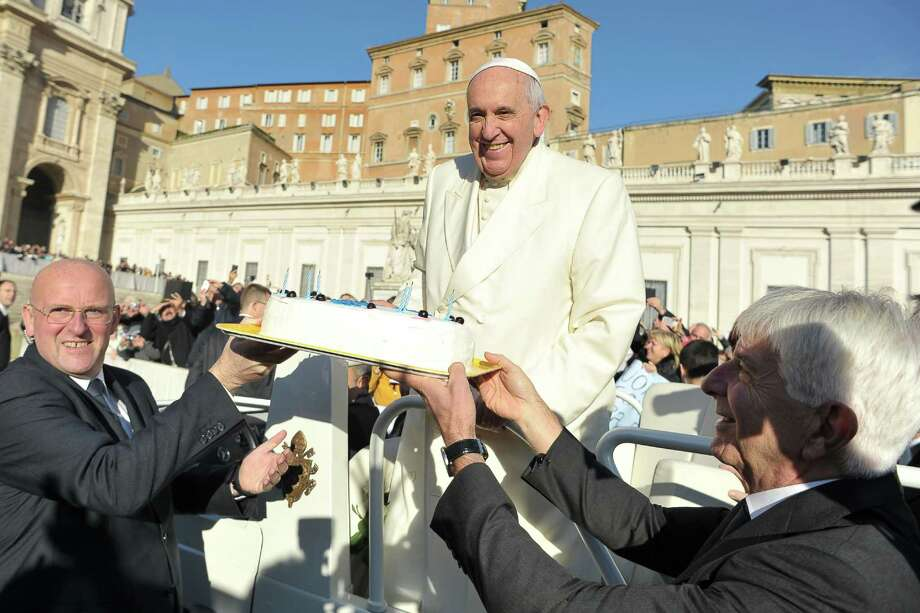 In this photo provided by Vatican newspaper L'Osservatore Romano, Pope Francis is presented with a cake during his weekly general audience in St. Peter's Square at the Vatican, Wednesday, Dec. 17, 2014. Pope Francis got a cake, cards and a tango demonstration for his 78th birthday Wednesday, and 800 kilograms of chicken meat for the poor. (AP Photo/L'Osservatore Romano) Photo: AP / L' Osservatore Romano