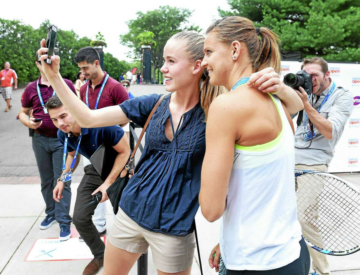 Alex Page, center, of New London takes a selfie with Lucie Safarova at the Connecticut Open.