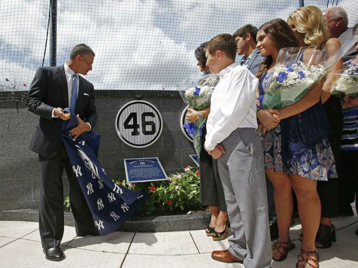 Retired New York Yankees pitcher Andy Pettitte unveils his No. 46 in Yankee Stadium's Monument Park as his family watches on Sunday.