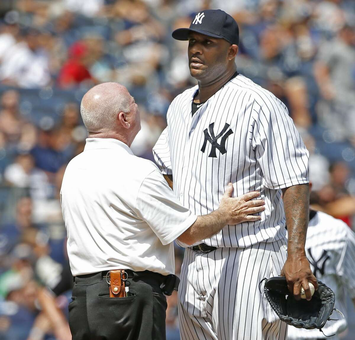 Yankees trainer Steve Donohue, left, talks to starting pitcher CC Sabathia in the third inning before manager Joe Girardi removed Sabathia from the game.