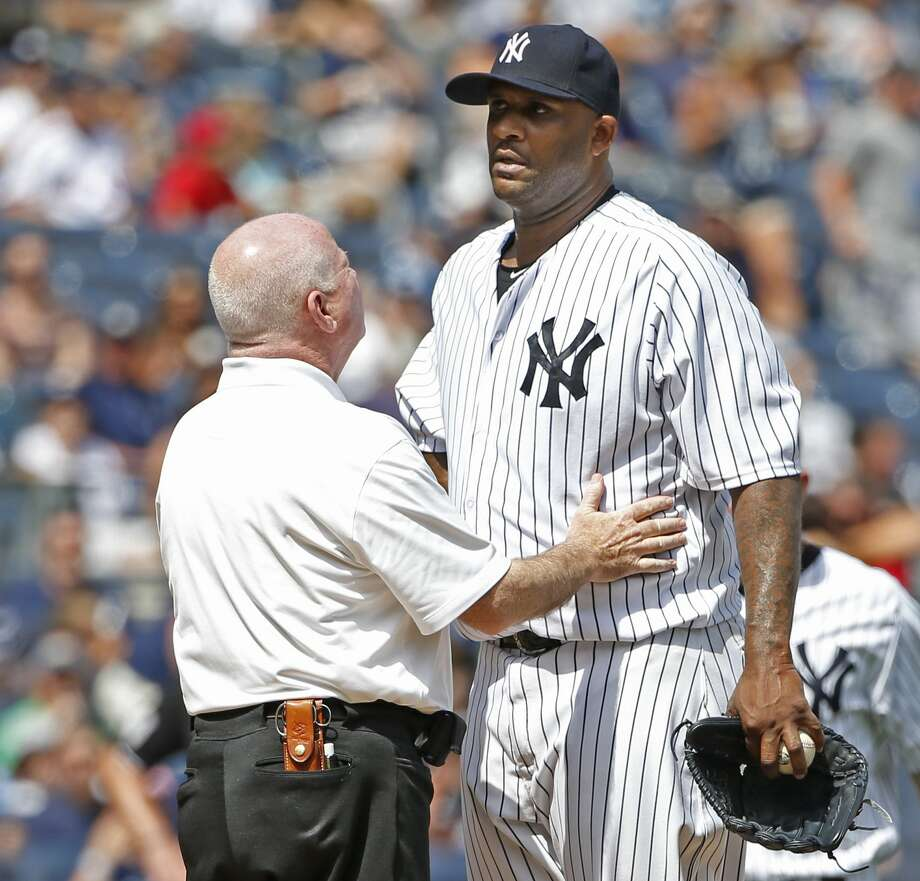Yankees trainer Steve Donohue, left, talks to starting pitcher CC Sabathia in the third inning before manager Joe Girardi removed Sabathia from the game. Photo: Kathy Willens — The Associated Press  / AP