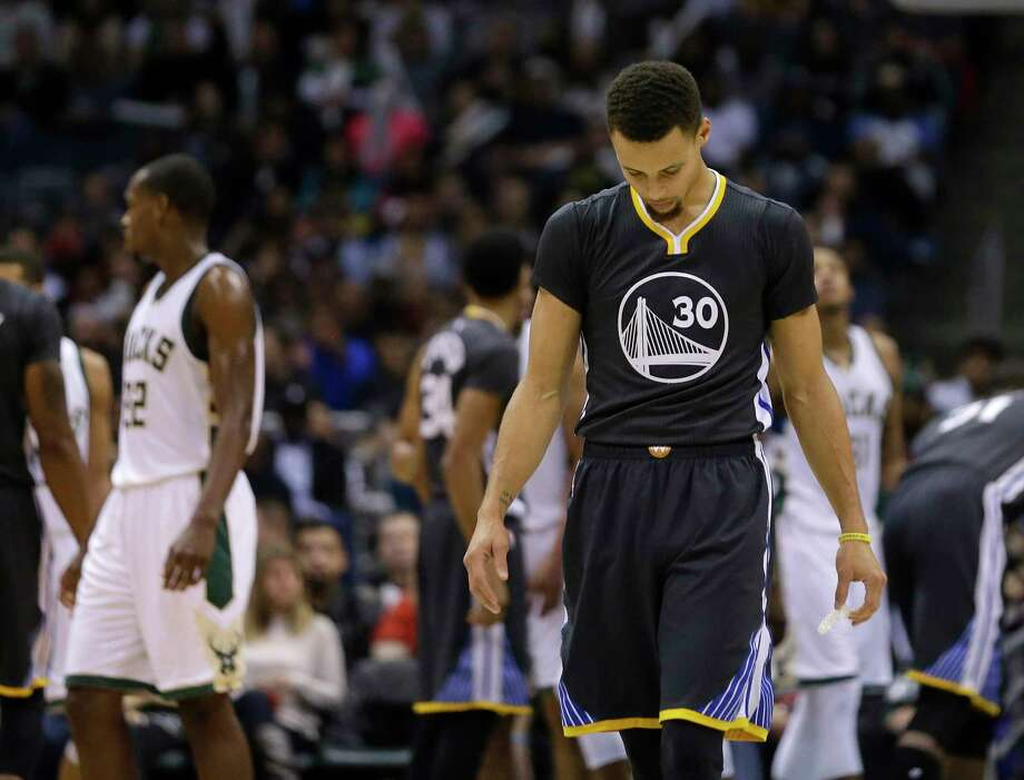 The Warriors' Stephen Curry looks down during the second half Saturday's loss to the Bucks. Photo: Aaron Gash — The Associated Press  / FR171181 AP