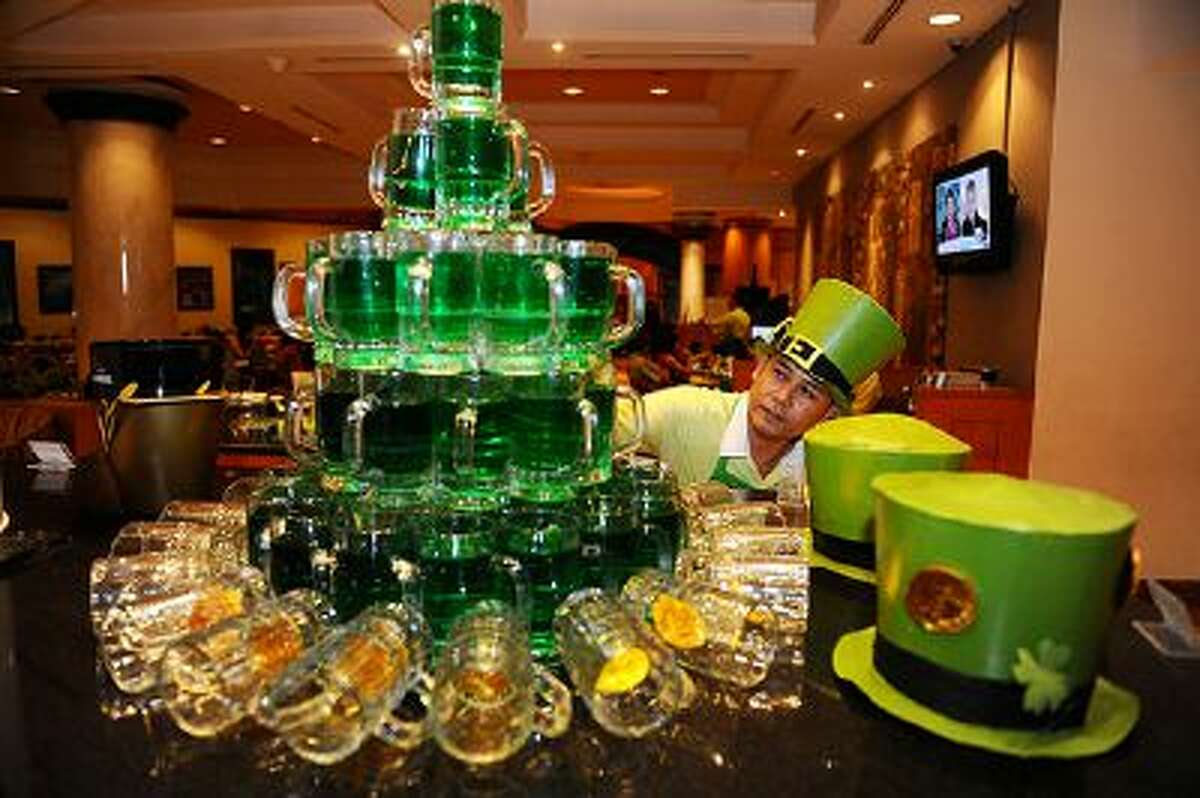 SURABAYA, INDONESIA - MARCH 14: A waitress prepares green beers during St. Patrick's Day celebrations at Sheraton Hotel on March 14, 2014 in Surabaya, Indonesia. Saint Patrick's Day is an annual religious and cultural celebration on March 17th commemorating the patron saint of Ireland. It is a public holiday in Northern Ireland, and the Republic of Ireland and is celebrated in a number of countries that have become home to the Irish diaspora. (Photo by Robertus Pudyanto/Getty Images)