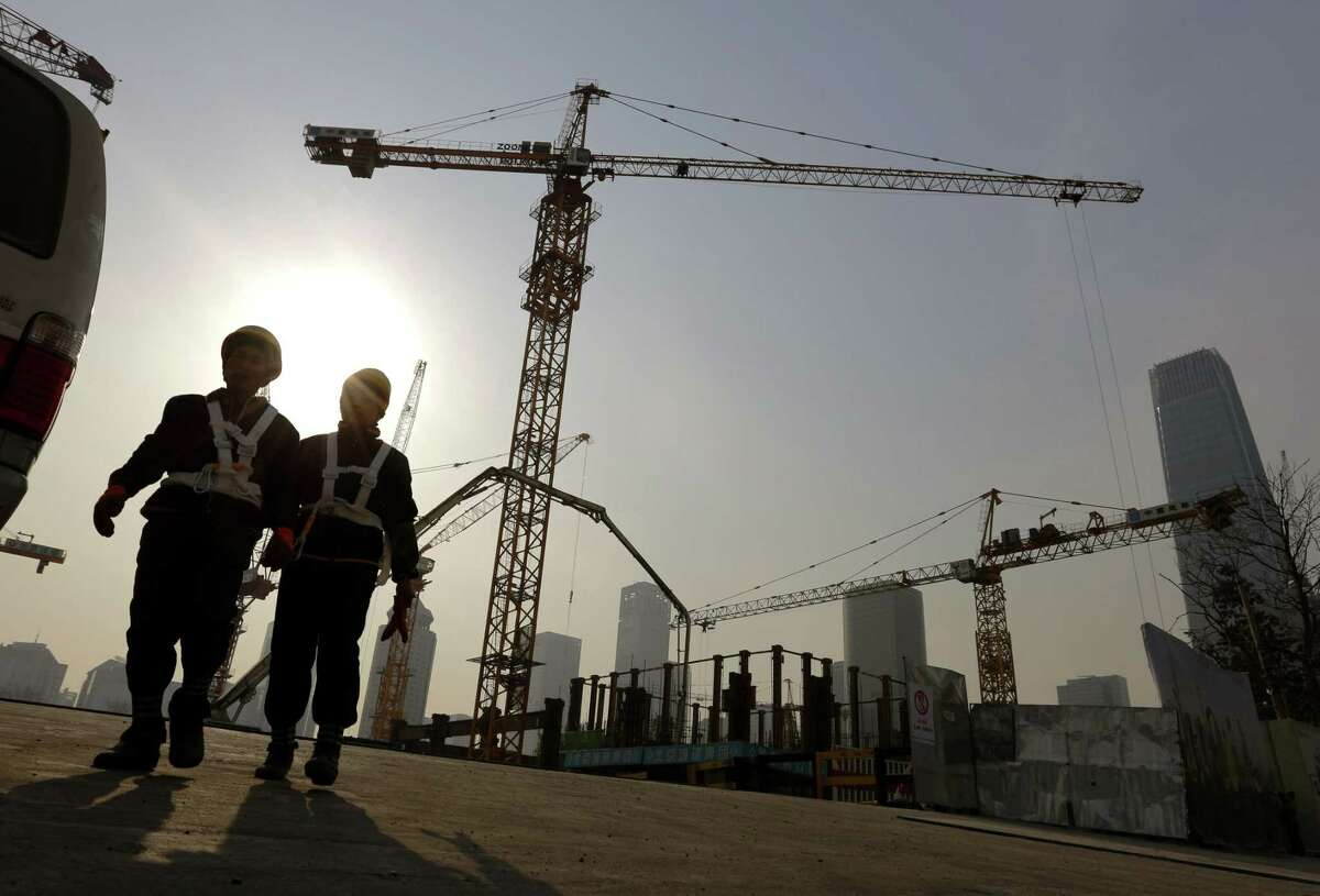 In this Jan. 20, 2015 photo, workers walk out from a construction site at the Central Business District of Beijing, China.