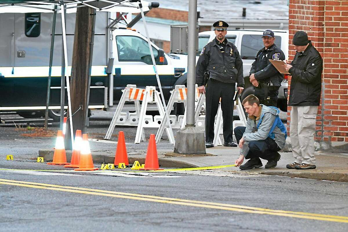 Investigators at the crime scene in Torrington Friday morning where police say a woman, 19, was stabbed to death.