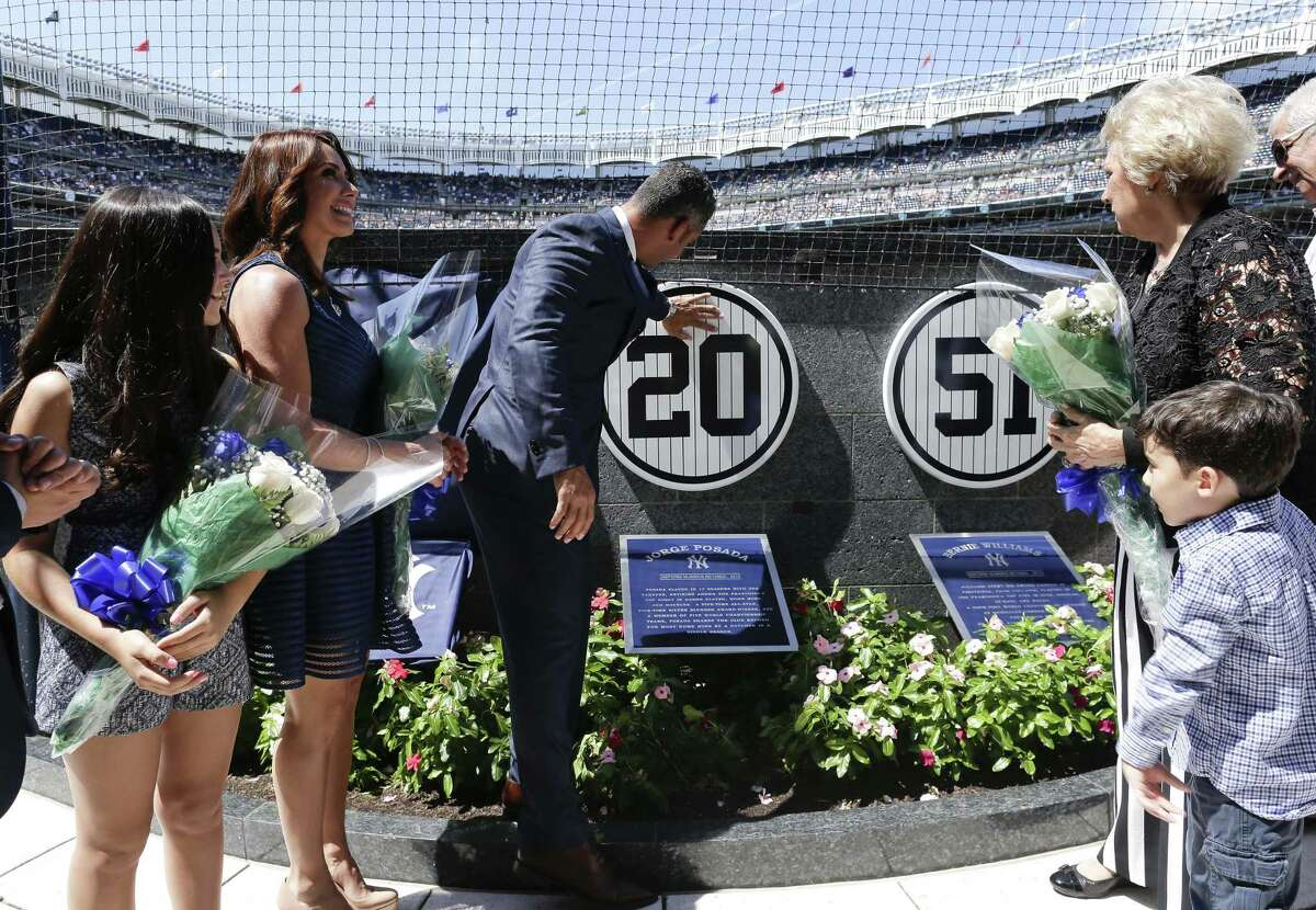 Former New York Yankees catcher Jorge Posada, third from left, and his wife Laura Posada, look at Posada's retired No. 20.