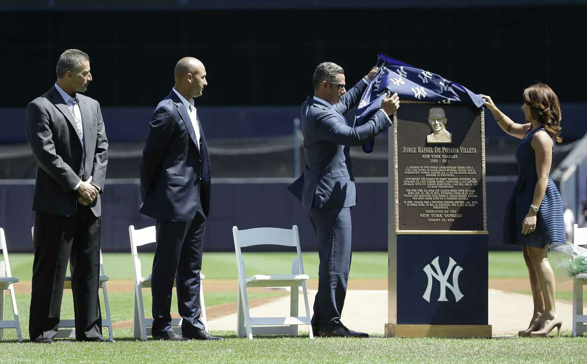 Jorge Posada, third from left, and his wife Laura Posada, unveil Posada's plaque that will hang at Monument Park.
