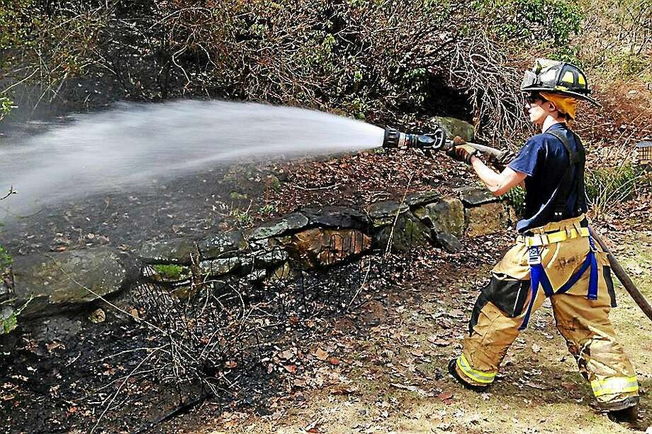 Haddam Fire Company crews helped knock down a brush fire Thursday in the woods behind a home on Beaver Meadow Road. It has spread after the homeowner was burning leaves. Photo: Courtesy Olivia Drake