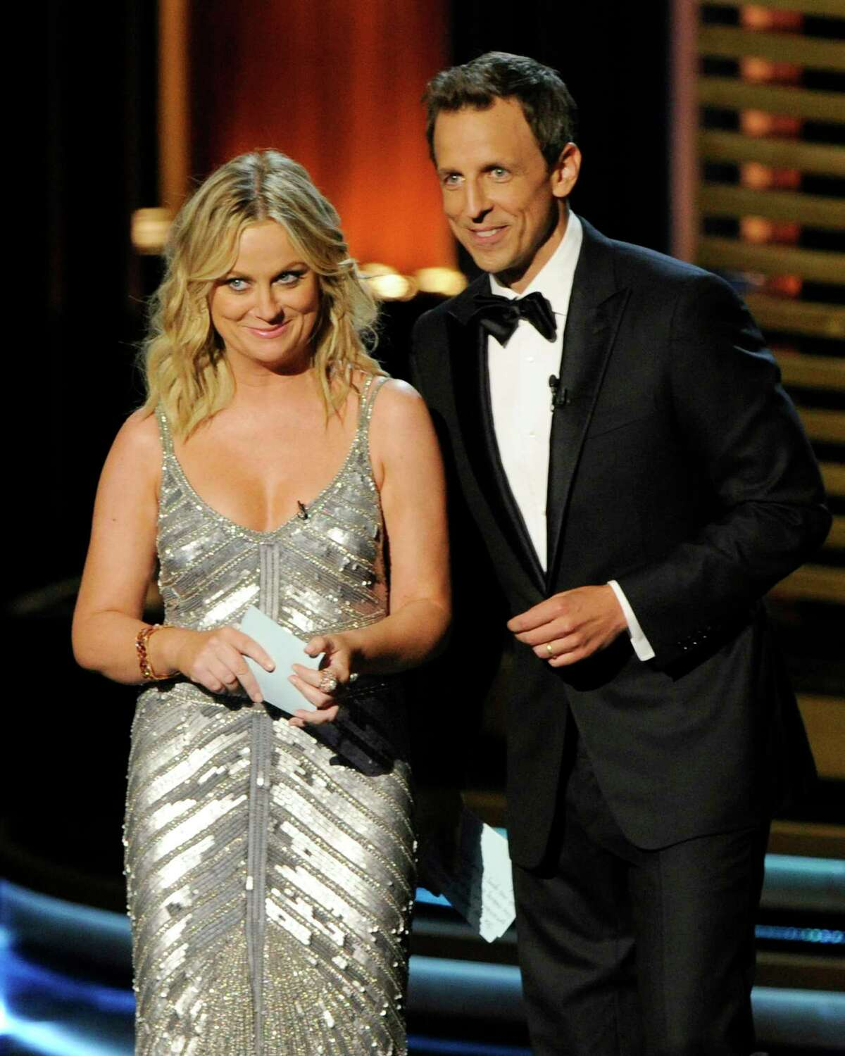 Amy Poehler, left, and Host Seth Meyers speak on stage at the 66th Annual Primetime Emmy Awards at the Nokia Theatre L.A. Live on Monday, Aug. 25, 2014, in Los Angeles.