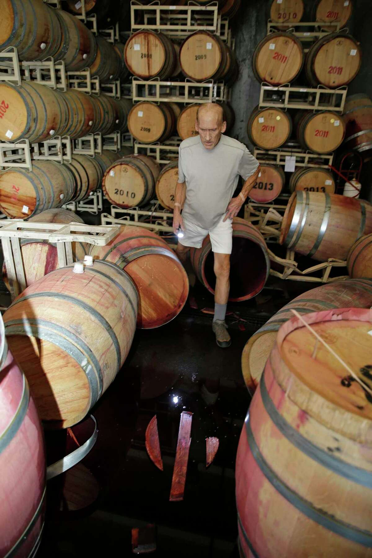 Winemaker Tom Montgomery walks in wine and looks over damage following an earthquake at the B.R. Cohn Winery barrel storage facility Sunday, Aug. 24, 2014, in Napa, Calif. Winemakers in Californiaís storied Napa Valley woke up to thousands of broken bottles, barrels and gallons of ruined wine as a result of Sundayís earthquake. (AP Photo/Eric Risberg)