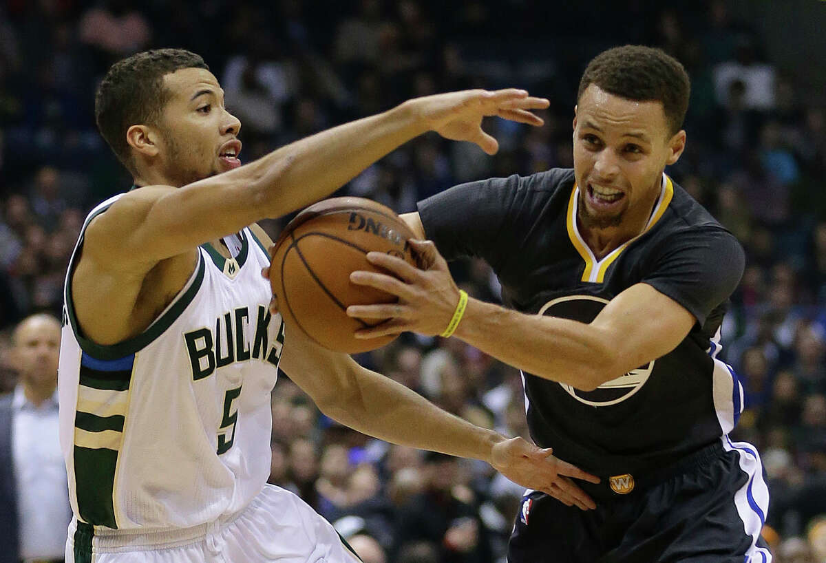 The Warriors' Stephen Curry, right, drives against the Bucks' Michael Carter-Williams during the first half Saturday.