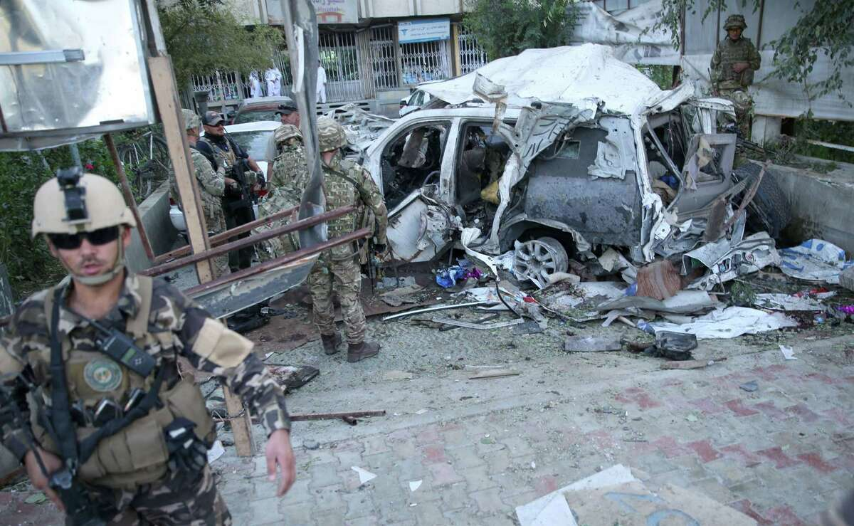 Afghan security forces and British soldiers inspect the site of a suicide attack in the heart of Kabul, Afghanistan, Saturday, Aug. 22, 2015. The suicide car bomber attacked a NATO convoy traveling through a crowded neighborhood in Afghanistan's capital Saturday, killing at least 10 people, including three American NATO contractors, authorities said.